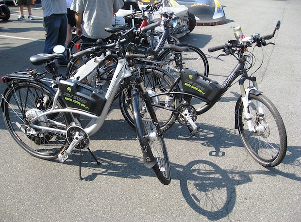 Two electric bikes parked among other bikes