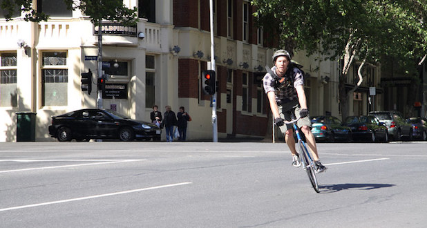 Cyclist taking a corner while pedalling a fixie