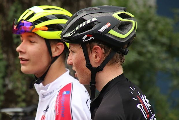 A pair of young cyclists in helmets, sweating profusely